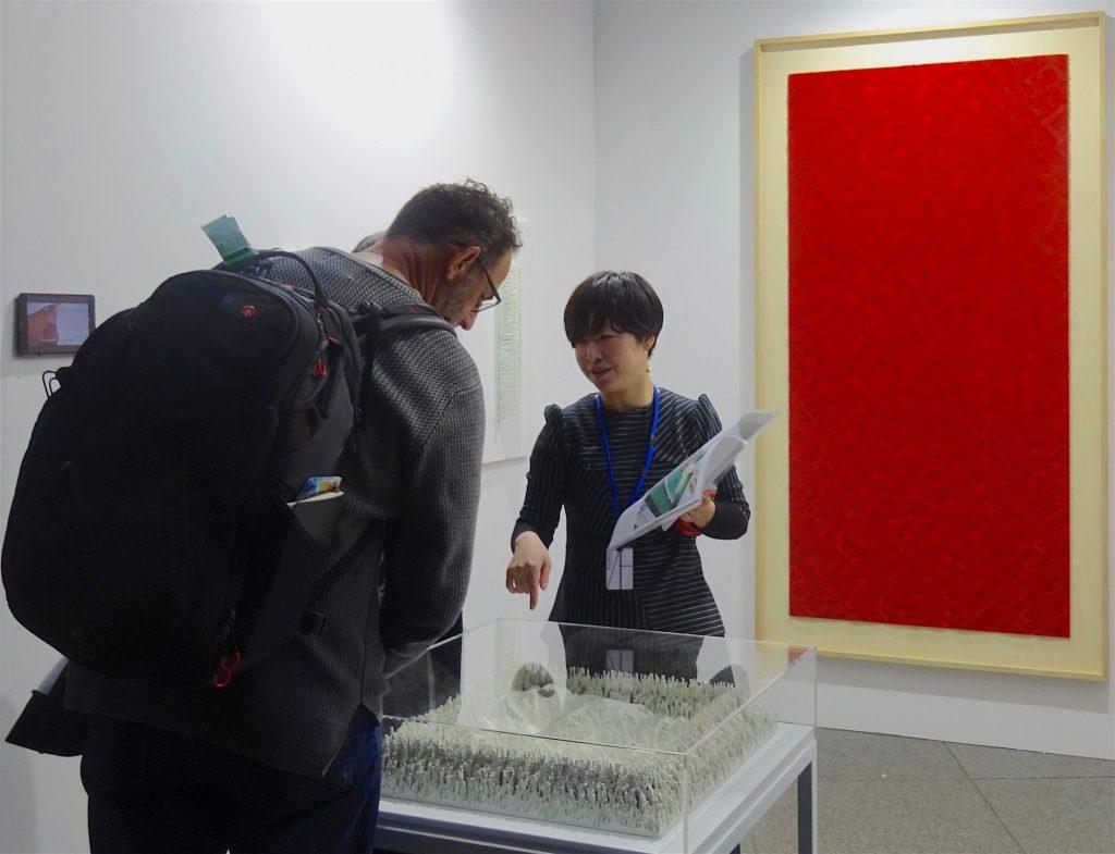 KAYOKOYUKI booth, gallery owner YUKI Kayoko 結城 加代子, explaining the works by IMAMURA Yohei 今村洋平