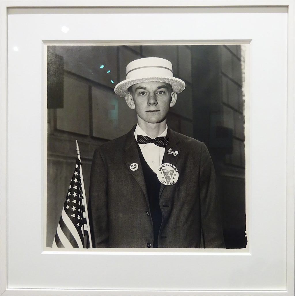 """Diane Arbus """"A Boy with a Straw Hat Waiting to March in a Pro-War Parade (N.Y.C. 1967)"""""""