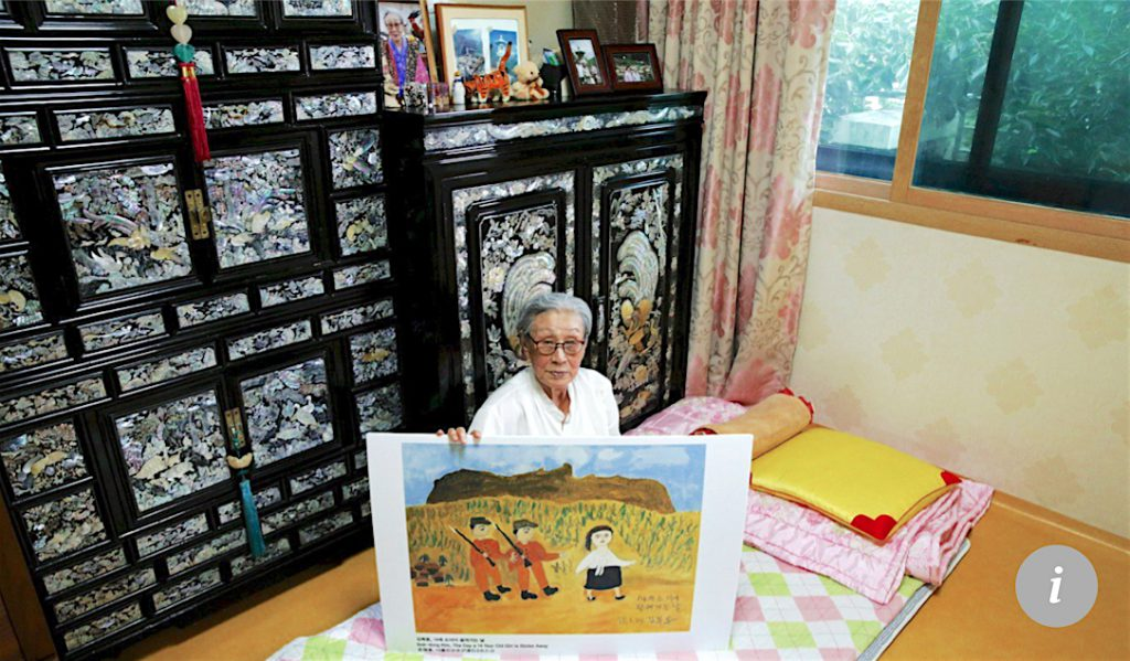 Kim Bok-dong poses with a copy of her painting, The Day A 14-year-old Girl Is Stolen Away, in 2015