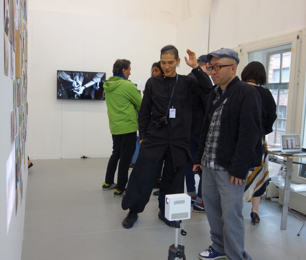 LISTE 2019, booth of MUJIN-TO Production 無人島プロダクション, artist TAGUCHI Yukihiro 田口 行弘 with collector YOSHINO Seiichi 吉野誠一