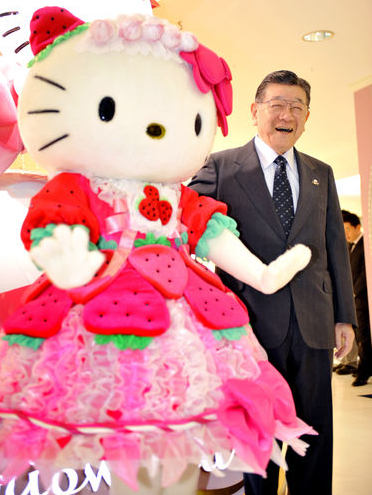 Shintaro Tsuji, founder and president of Sanrio Co., smiles as he poses with a Hello Kitty model at a Sanrio shop in Tokyo