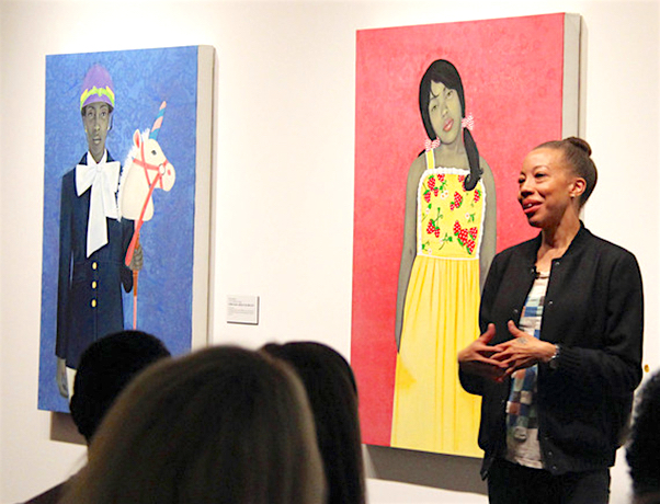 Amy Sherald lecturing in front of her paintings