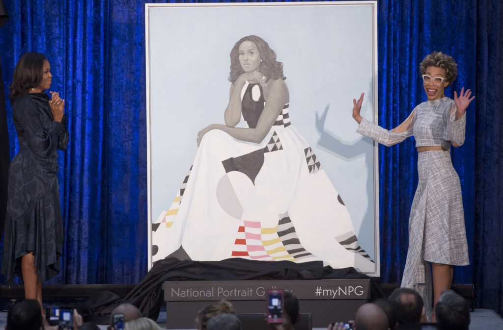 Former First Lady Michelle Obama and Amy Sherald stand next to Mrs. Obama's portrait at the Smithsonian National Portrait Gallery