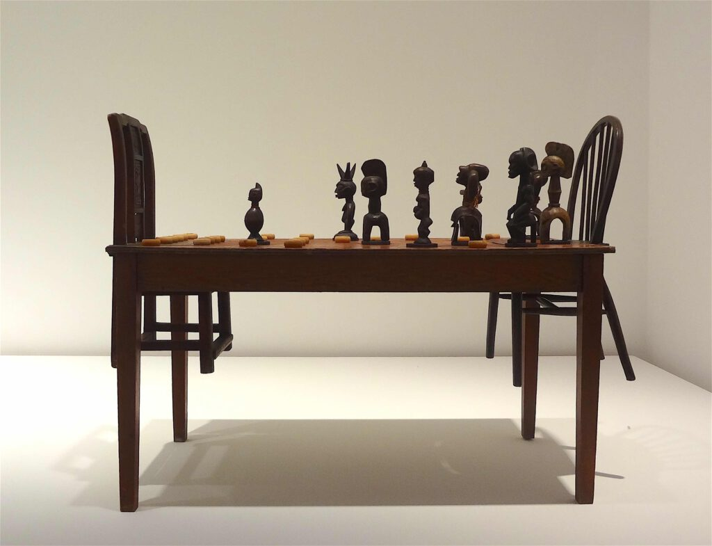 """Chen Zhen """"Couldn't Bananas Be Black"""" 1999, Wood, chairs, African statuettes, Chinese chess"""