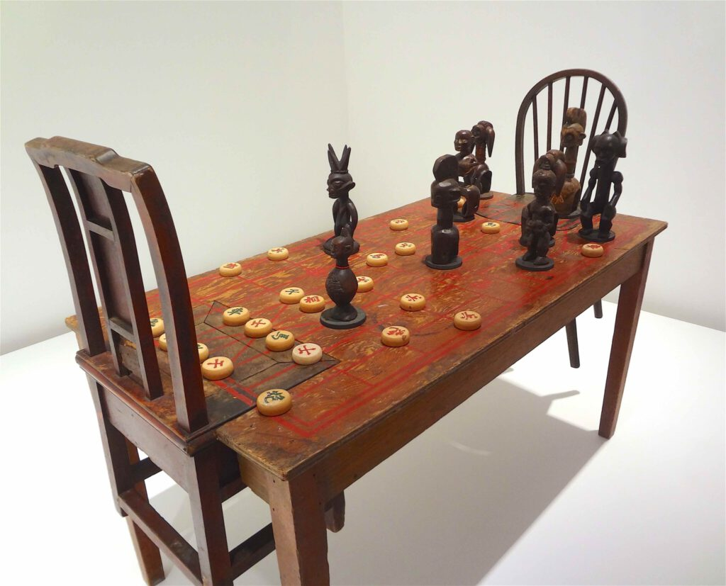 """Chen Zhen """"Couldn't Bananas Be Black"""" 1999, Wood, chairs, African statuettes, Chinese chess, detail1"""