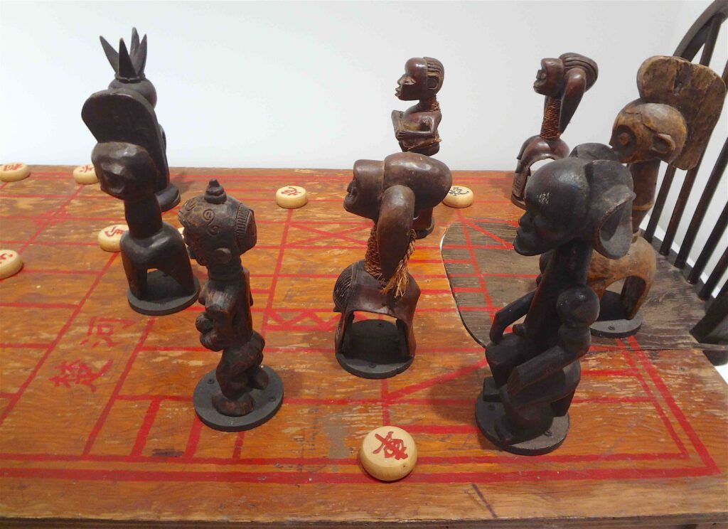"""Chen Zhen """"Couldn't Bananas Be Black"""" 1999, Wood, chairs, African statuettes, Chinese chess, detail2"""