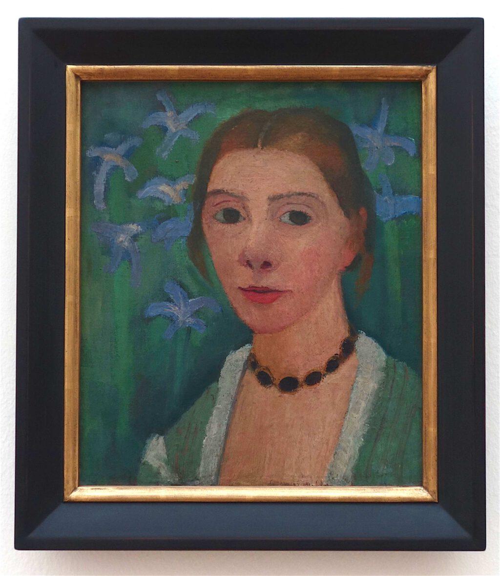 ポーラ・モデルソン=ベッカー「緑の背景に青いアイリスを配した自画像」キャンバスにオイルテンペラ、40.7 x 43.5 センチ、約1905年 (Kunsthalle Bremen)
